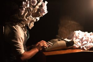 A-man-sitting-at-a-typewriter-to-apply-for-a-conservation-job-has-paper-exploding-out-of-his-head